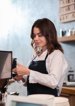 Vrouwelijke werknemer die koffie maakt