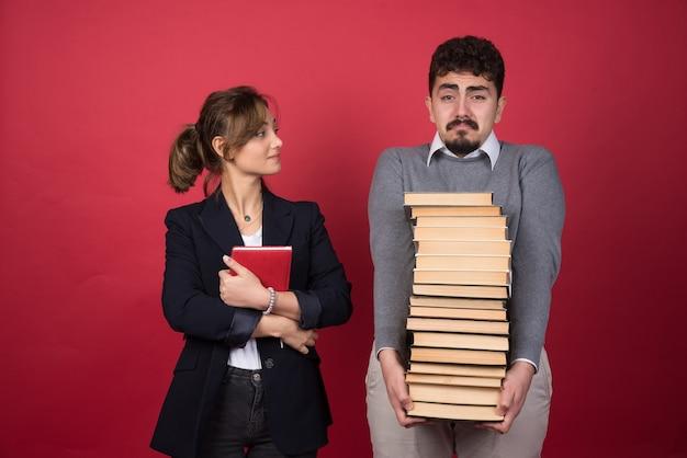 Vrouwelijke werknemer die man met een heleboel boeken bekijkt