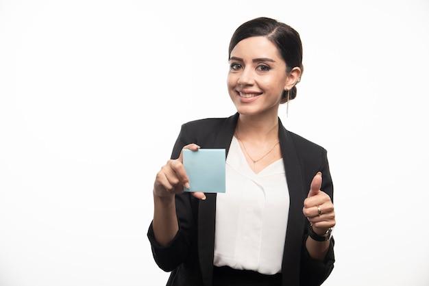Vrouwelijke werknemer die memoblok vasthoudt en duimen opgeeft. hoge kwaliteit foto