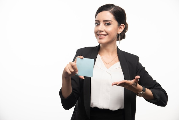 Vrouwelijke werknemer die memostootkussen op witte achtergrond toont. hoge kwaliteit foto
