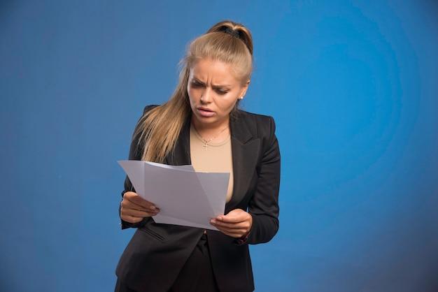 Vrouwelijke werknemer die papieren documenten controleert.