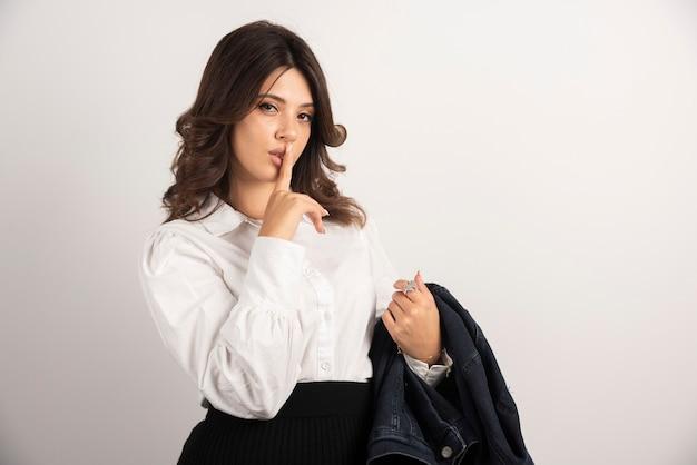Vrouwelijke werknemer die stilteteken op wit maakt.