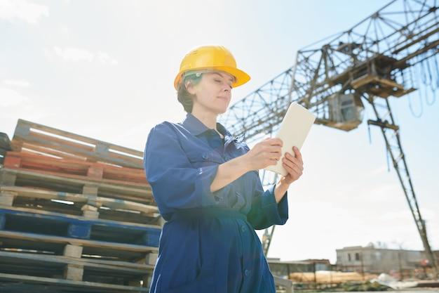 Vrouwelijke werknemer die tablet in zonlicht gebruiken