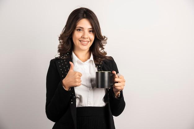 Vrouwelijke werknemer die thee vasthoudt en duimen opgeeft