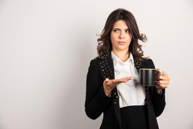 Vrouwelijke werknemer die thee vasthoudt met een boze uitdrukking
