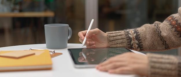 Vrouwelijke werknemer die van huis met modeltablet en kantoorbehoeften aan koffietafel werken