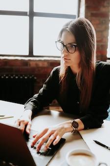 Vrouwelijke werknemer die werkt in het kantoor met grote ramen