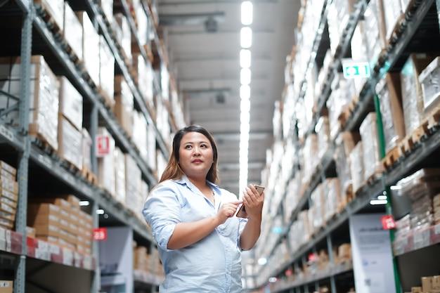 Vrouwelijke werknemer doos met producten inspecteren tijdens het werken in groot magazijn