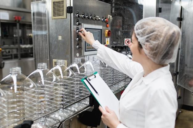 Vrouwelijke werknemer in bottelarij die waterflessen controleert vóór verzending. inspectie kwaliteitscontrole.
