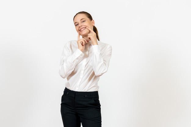 Vrouwelijke werknemer in een elegante witte blouse lachend op wit