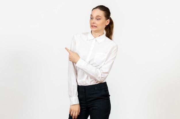 Vrouwelijke werknemer in een elegante witte blouse met een verward gezicht op wit