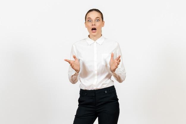 Vrouwelijke werknemer in elegante witte blouse met geschokt gezicht op wit