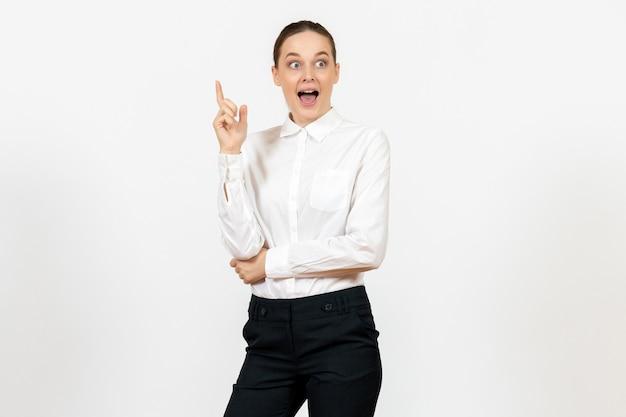 Vrouwelijke werknemer in elegante witte blouse met opgewonden gezicht op wit