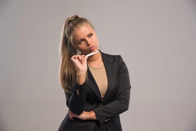 Vrouwelijke werknemer in zwart pak denken.