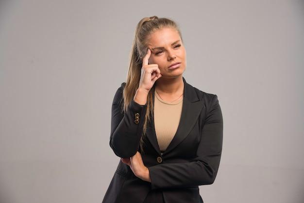 Vrouwelijke werknemer in zwart pak kijkt twijfelachtig.