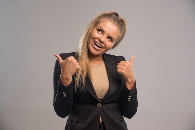 Vrouwelijke werknemer in zwart pak maakt duimen omhoog en plezier.