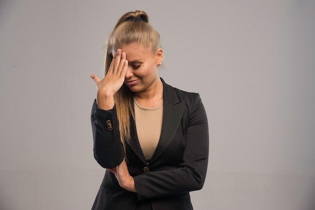 Vrouwelijke werknemer in zwart pak schaamt zich.