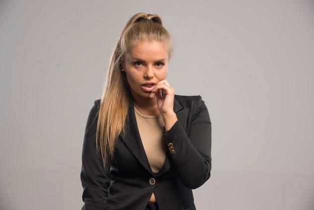 Vrouwelijke werknemer in zwart pak ziet er attent uit.