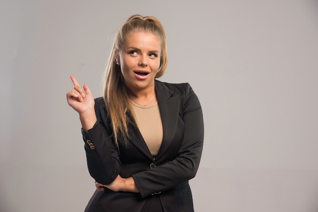 Vrouwelijke werknemer in zwart pak ziet er positief uit.