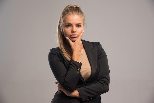 Vrouwelijke werknemer in zwart pak ziet er serieus uit.