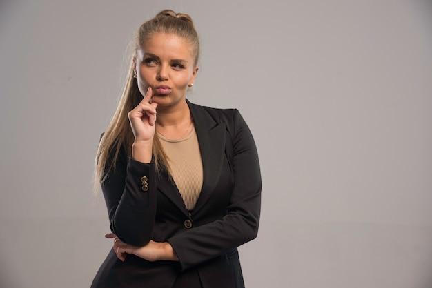 Vrouwelijke werknemer in zwart pak ziet er spijtig uit.