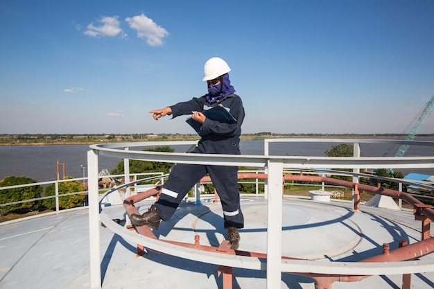 Vrouwelijke werknemer inspectie visuele dak opslagtank olie