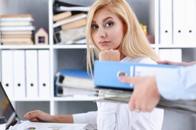 Vrouwelijke werknemer laat pak documenten aan manager zien