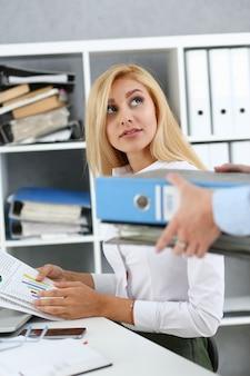 Vrouwelijke werknemer laat pak documenten zien te druk