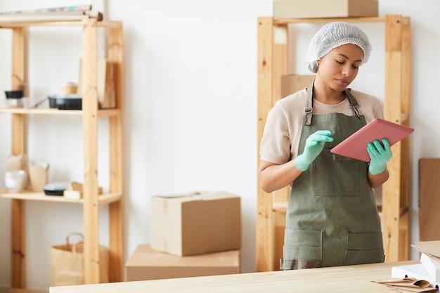 Vrouwelijke werknemer met behulp van digitale tablet tijdens het werken in de keuken bij de bezorgservice voor eten