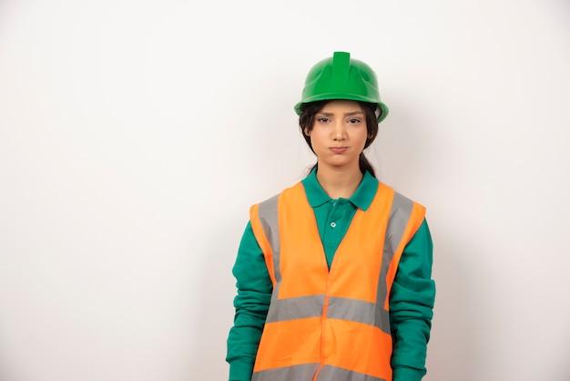 Vrouwelijke werknemer met boos gezicht op witte achtergrond.
