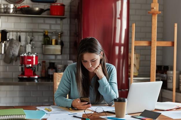 Vrouwelijke werknemer met donker lang haar, gekleed in een stijlvol shirt, maakt gebruik van mobiele telefoon, werkt aan bedrijfsrapport, drinkt afhaalkoffie, gebruikt laptop,