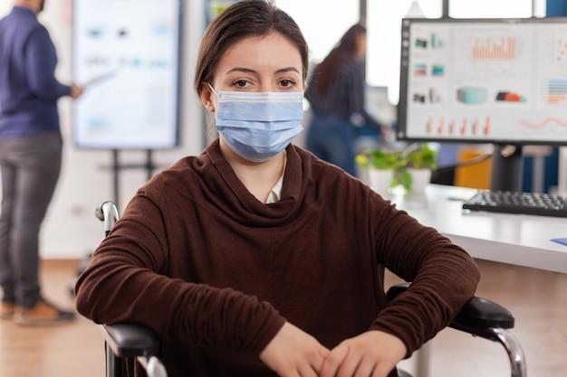 Vrouwelijke werknemer met een handicap met beschermingsmasker tegen coronavirus naar voren kijkend