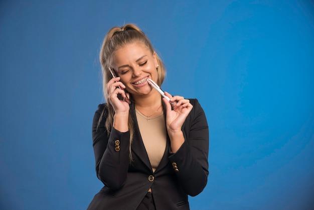 Vrouwelijke werknemer met telefoongesprek terwijl ze een pen met haar mond vasthoudt en lacht.