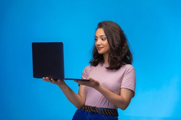 Vrouwelijke werknemer met zwarte laptop die videogesprek heeft en glimlacht.
