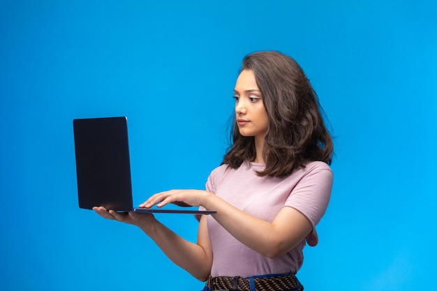 Vrouwelijke werknemer met zwarte laptop die videogesprek heeft.
