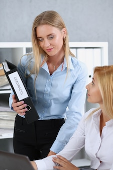 Vrouwelijke werknemer toont pakje documenten aan drukke manager