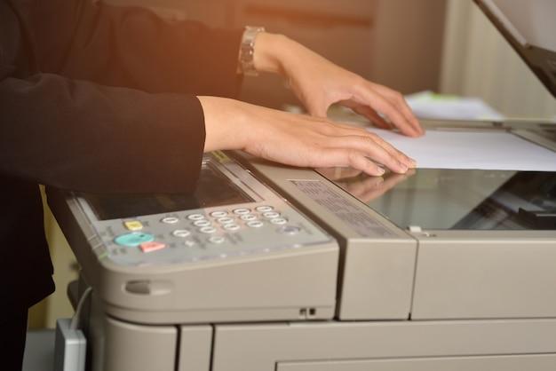 Vrouwelijke werknemers gebruiken een kopieermachine op kantoor.