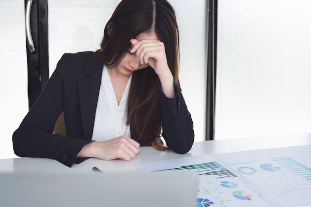 Vrouwelijke werknemers vertonen hoofdpijn door werk of teleurstelling door werk.