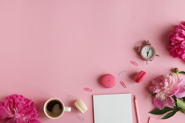 Vrouwelijke werkplek met notitieblok potlood wekker pioenroos bloemen kopje koffie en macarons