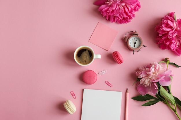 Vrouwelijke werkplek met notitieblok potlood wekker pioenroos bloemen plaknotities koffie macarons