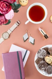 Vrouwelijke werkruimte met dagboek, bloemen, snoep, modeaccessoires.