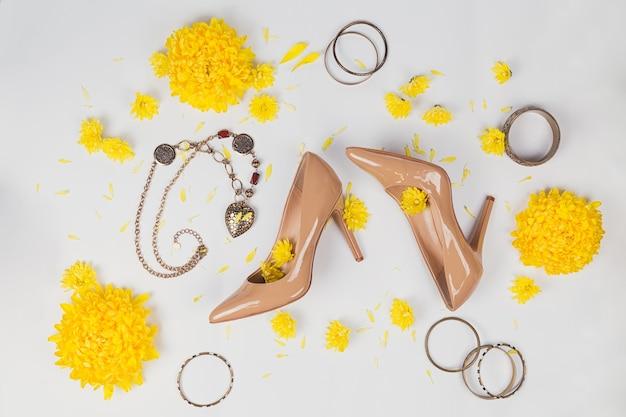 Vrouwelijke werkruimte met gele bloemen en damesaccessoires: hoge hakken en armbanden, op een witte achtergrond. platliggend bureau met bovenaanzicht.