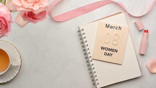 Vrouwelijke werkruimte met notitieboekje, theekop, bloemen, lint, lippenstift en bericht