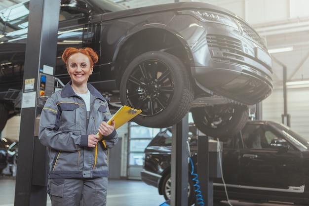 Vrouwelijke werktuigkundige die bij autobenzinestation werkt