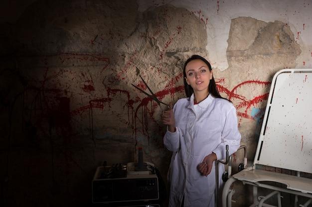 Vrouwelijke wetenschapper die een grote ijzeren schaar vasthoudt in een kerker met bloedige muren in een halloween-horrorconcept