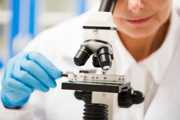 Vrouwelijke wetenschapper die materiaal op de microscoop analyseert