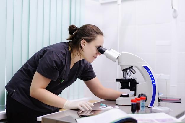 Vrouwelijke wetenschapper die nieuwe substantie of virus in microscoop bestudeert