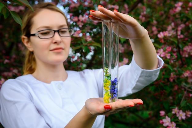 Vrouwelijke wetenschapper in glazen met reageerbuizen in handen bestudeert de eigenschappen van planten in de botanische tuin