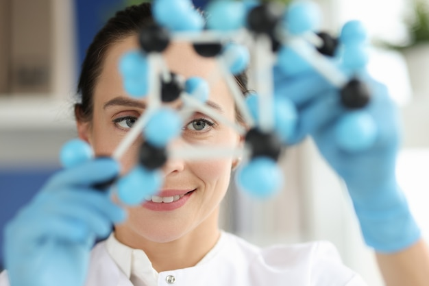 Vrouwelijke wetenschapper kijkt naar dna-lay-outeigenschappen van stoffen zijn afhankelijk van structuur en
