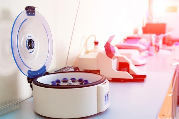 Vrouwelijke wetenschapper laadt enkele flesjes vloeistof in een centrifuge in een laboratorium.